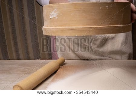 A Woman Sifts Flour Through A Sieve. Plywood Cutting Board, Wooden Flour Sieve And Wooden Rolling Pi