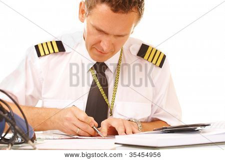 Airline pilot wearing shirt with epaulets and tie filling in and checking papers flight plan, weather forecast. Headset on the table.