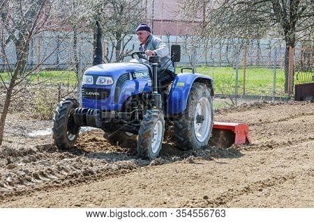 Uzhhorod, Ukraine, 1 April 2019: Farmer Plows The Field. Small Tractor With A Plow In The Field. Cul