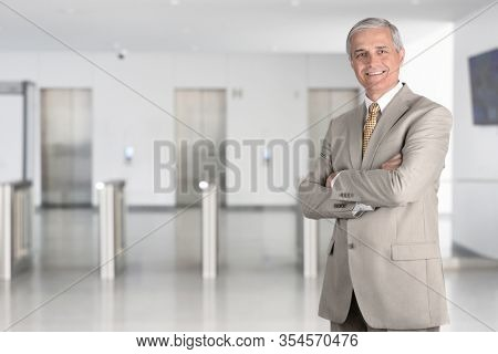 A smiling middle aged businessman with arms folded in a modern office lobby. Blurred background with elevators and turnstiles and copy space.