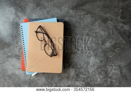 Stack Of Books On Abstract Cement Background.