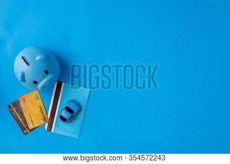 Piggy Bank And Savingbook On Blue Background With Copy Space.