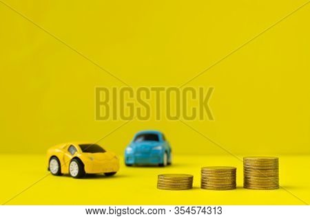 Toy Cars And Stack Of Money On Yellow Background.