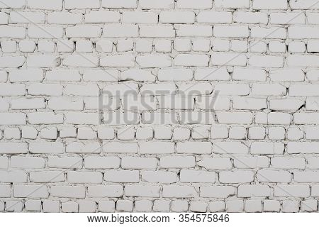 An Old Brick Wall Of Rectangular Bricks With Inaccurate Seams, Covered With Whitewash. Painted Vinta