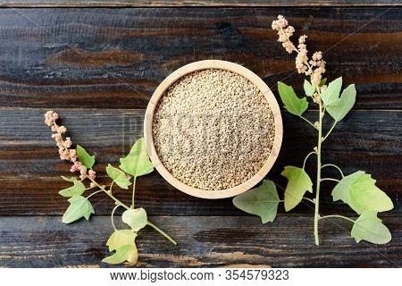 Organic Raw Brown Quinoa Seed (chenopodium Quinoa) In A Bowl And Quinoa Plant On Wooden Background,