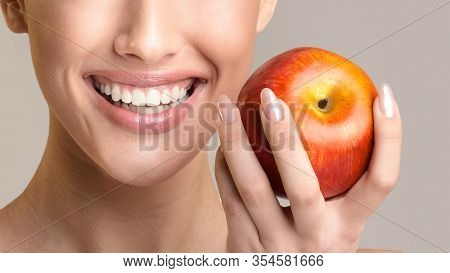 Toothcare. Unrecognizable Girl With Perfect Healthy Teeth Holding Red Apple And Smiling Posing Over