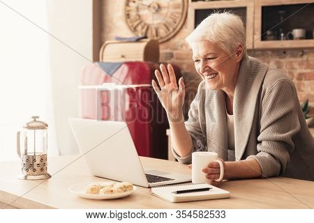 Elderly Woman Making Video Call On Laptop In Kitchen, Waving At Screen, Chatting With Children, Free