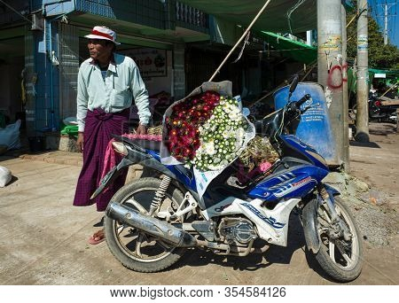 Mandalay, Myanmar - January 12, 2019: Flower market, Flower delivery on motorbike. Burmese man standing next to motorbike with big bunch of chrysanthemum flowers on sit