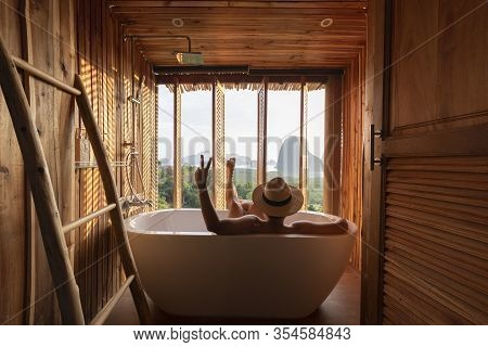 A Man Is Enjoy Life By Sitting In The Bath Tub And Looking At The Beautiful View Of Samed Nang She O