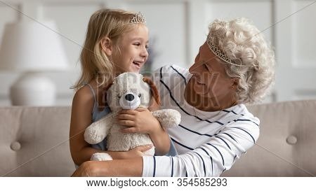 Happy Mature Grandmother And Little Granddaughter Play Together