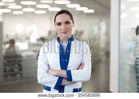 Beautiful Young Woman In Lab Coat Crossing Arms