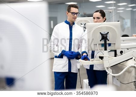 Research Scientists Using Automated Immunoassay System In Lab