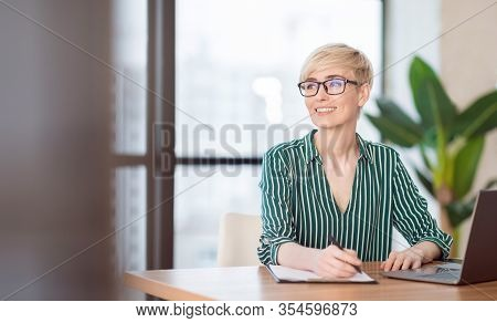 Business Career. Smiling Business Lady Taking Notes Looking Aside Sitting In Modern Office. Selectiv