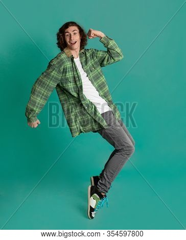 Happy Young Man Standing On Tiptoes Against Color Background
