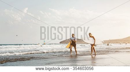 Surfer Couple Running Long Sea Shore Ready To Surf On High Waves - Sporty Friends Having Fun During