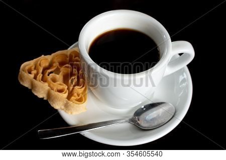 A Cup Of Coffee And A Biscuit On A Blcak Background