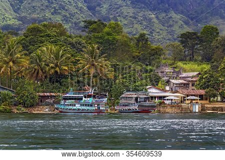 Parapat, Indonesia - January 1, 2020. Berth For Pleasure Boats And Ferries On Lake Toba Against A Ba