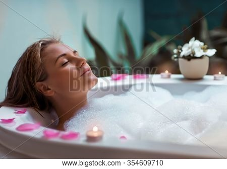 Portrait of a beautiful young woman taking bath with foam by candlelight, enjoying dayspa in luxury spa hotel