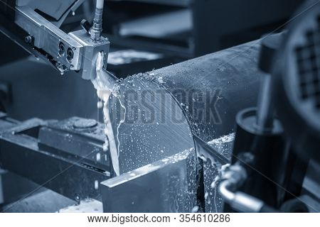 The Operation Of Automatic Band Saw Machine Cutting The Metal Shaft With Liquid Coolant . The Materi