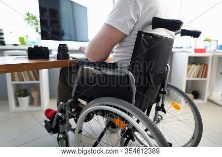 Close-up Of Man Sitting In Disabled Carriage And Looking In Computer Screen. Adapted Workplace And O