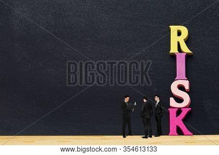 Arrangement Wooden Letters Word Risk With Miniature Figurine Businessmen Ceo, Cfo Talk On Blackboard