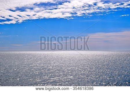 View Of The Blue Sky With White Clouds Over The Silvery Sea. The Water Glistens In The Sun.