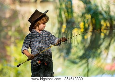 Catch Fishing. The Boy Catches A Big Fish With A Fishing Rod. Weekend In The Wild Nature.