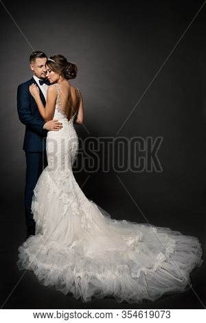 Wedding Couple, Beautiful Bride In White Dress With Long Train Tail, Elegant Groom Kissing Romantic