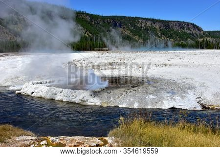 Black Sand Basin And The Cliff Geyser Erupting, Yellowstone National Park.