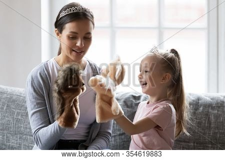 Happy Little Girl Wearing Crown Playing Hand Toys With Babysitter.