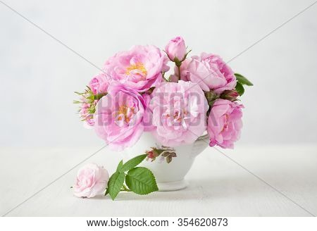 Small light pink bouquet of roses in porcelain vase against of pale grey background.  Shallow depth of field. Selective focus.