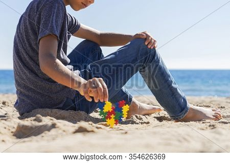 Autism Awareness Day Concept. Boy Teenager Sitting On The Beach With Colorful Puzzle Autism Awarenes