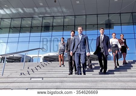Group Of Business People And Their Leader Walking Down Stairs Outside Office Building Successul Deal