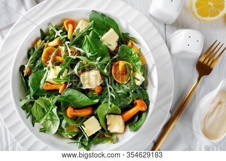 Arugula, Spinach, Honey Mushrooms, And Cubed Cheddar Cheese Salad In A White Bowl. Lemon Slices, Gol