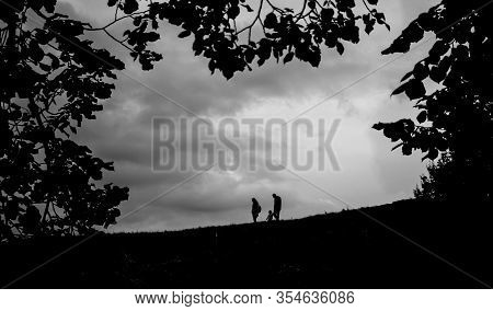 The Black Silhouette Of The Slope From Which A Family Of Three People Descends On A Background Of A