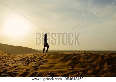 Single Young Asian Girl Stands On Top Of Sand Dune In Wind At Mingsha Mountain And Crescent Moon Spr