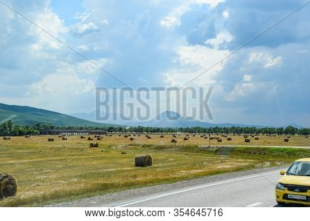 Krasnodar, Russia - June 13, 2019: Field With Bales Of Hay. Preparing Hay For Feeding Animals. Newly