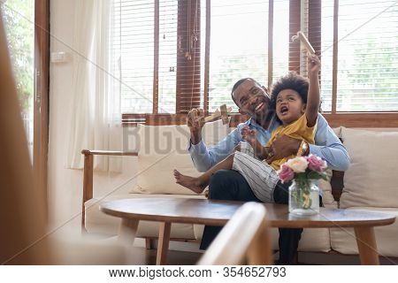Happy African Father And Little Child Son Spending Time Playing Wooden Airplane Toy At Home Together
