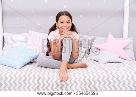 Comfortable And Cozy. Little Child Feel Comfortable At Home. Small Girl Sit In Bed. Cute Kid Wear Co