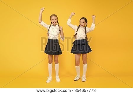 Together We Are Winners. Little Schoolchildren Making Winner Gestures On Yellow Background. Cute Sma