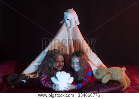 Childhood And Leasure Concept. Kids In Pajamas Covered With Blanket