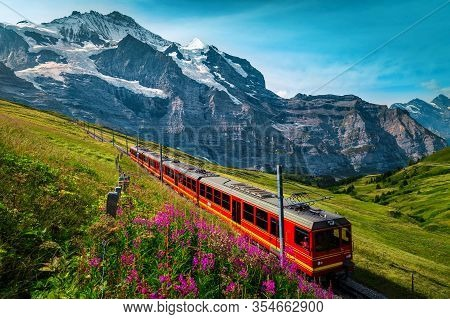 Fantastic Cogwheel Railway With Electric Red Tourist Train. Snowy Jungfrau Mountains With Glaciers,