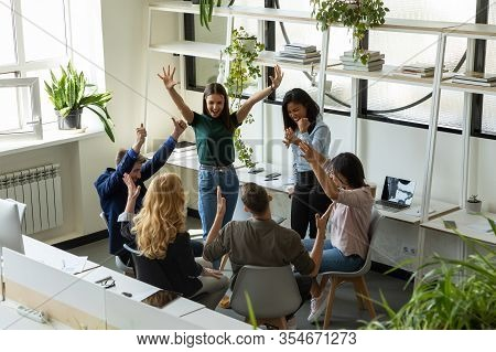 Overjoyed Diverse Colleagues Celebrate Group Success At Meeting