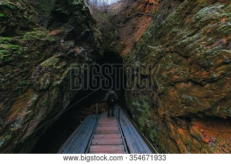 Traveler With A Backpack Getting Down Into The Cave By Wooden Stairs. Back View. In The Mountains