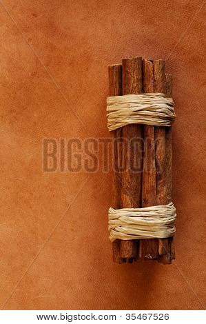 old weathered leather  background with cinnamon sticks stock photo image