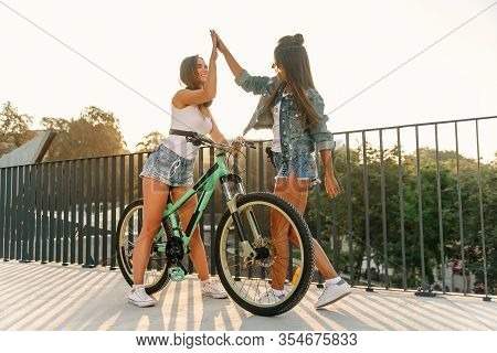 One Trendy 30s Girl With Bike Waiting For Her Hot Female Friend In Tempting Shorts On The Specially