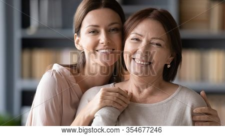 Portrait Young Affectionate Woman Cuddling Older Senior Mother.