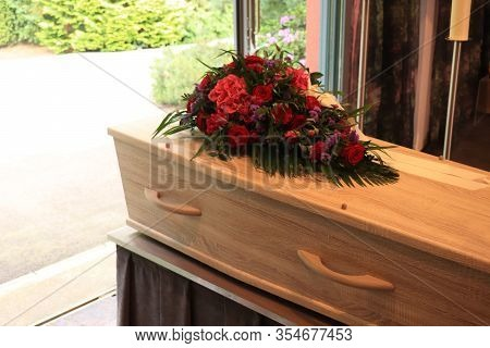 A Coffin With A Flower Arrangement In A Morgue, A Funeral Service