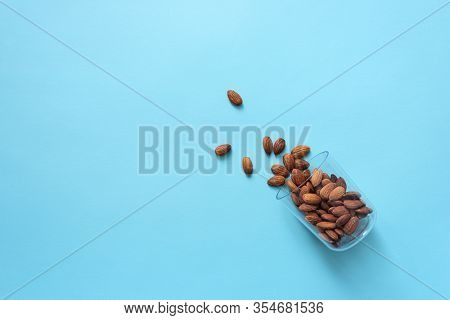 A glass lies on its side with almond nuts poured out of it. Top view healthy food background.