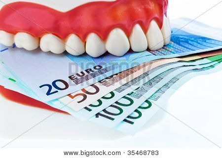 a tooth model at the dentist with euro notes. costs for health.